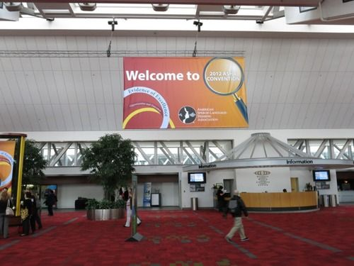 "The entrance to the Atlanta Convention Center for the 2012 ASHA Convention. Red carpet, tall ceiling, and a sign that reads ""Welcome to 2012 ASHA Convention with a magnifying glass as  part of the banner."