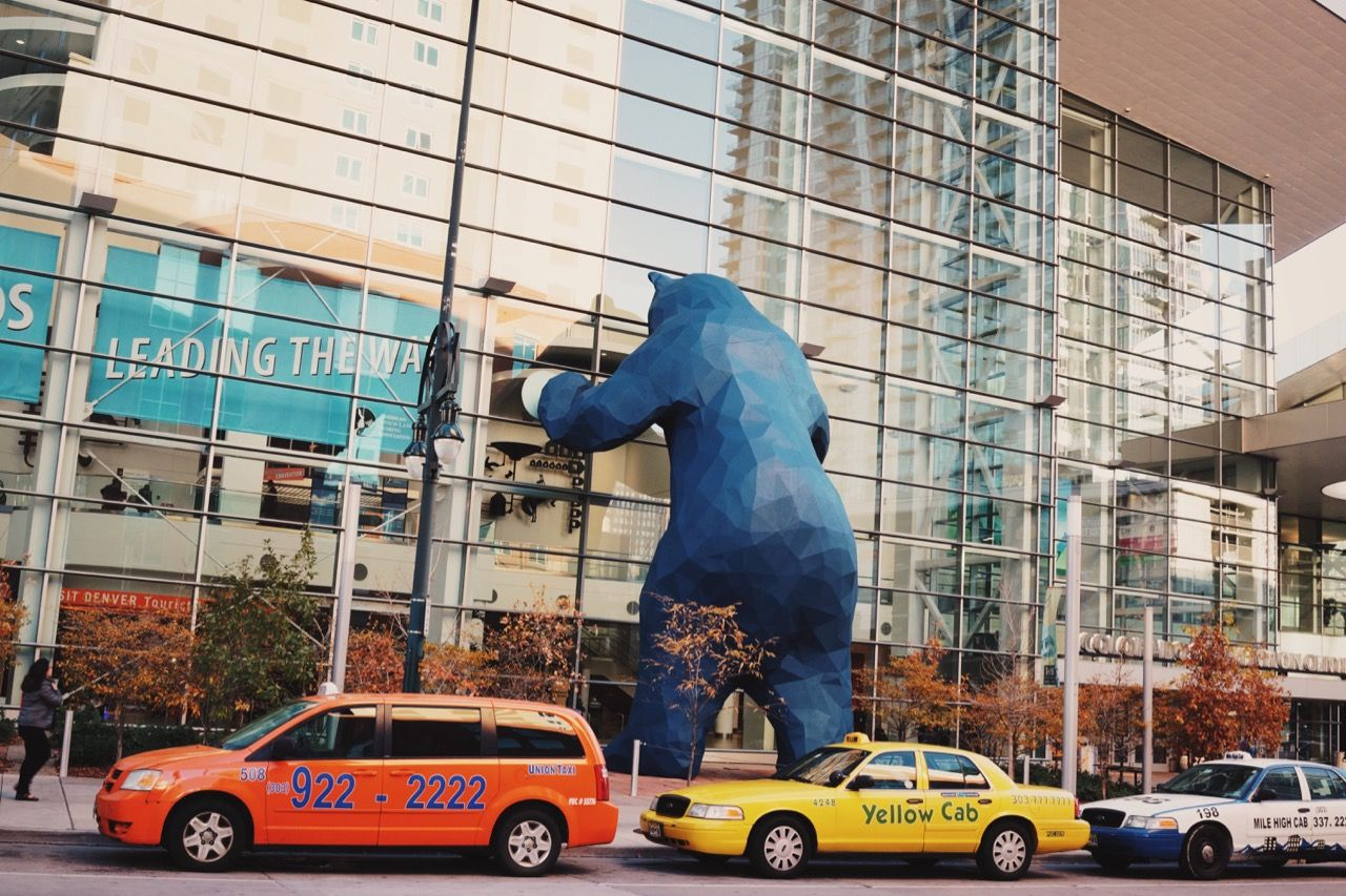 Exterior of Denver Convention Center. Taxis at curb, with large geometric blue bear statue facing large glass windows of convention center entrance.
