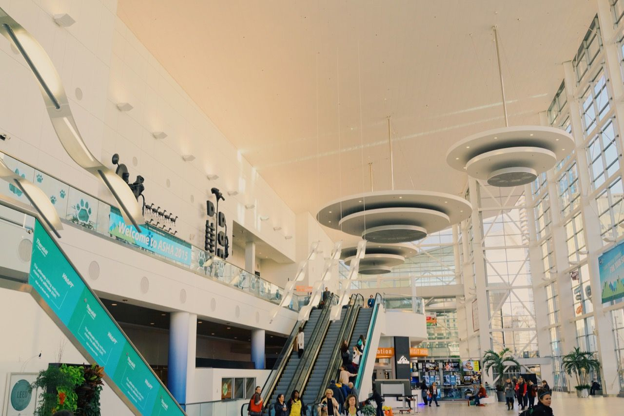 One entrance of the Denver Convention Center. First floor level looking towards escalators as well as snack and coffee vending in the distance.